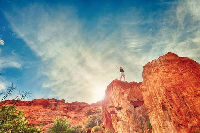 Femme heureuse sur un rocher rouge sous le ciel